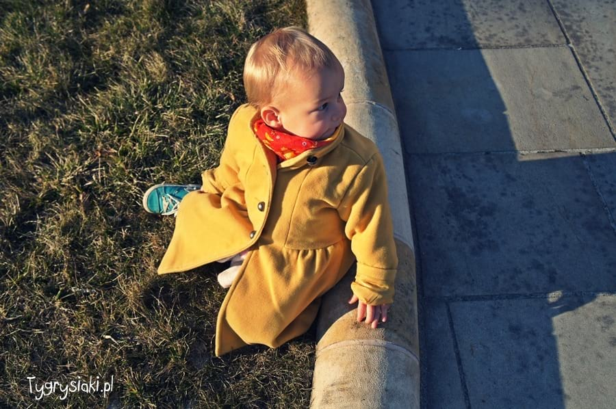 Mała dziewczynka wżółtym płaszczyku