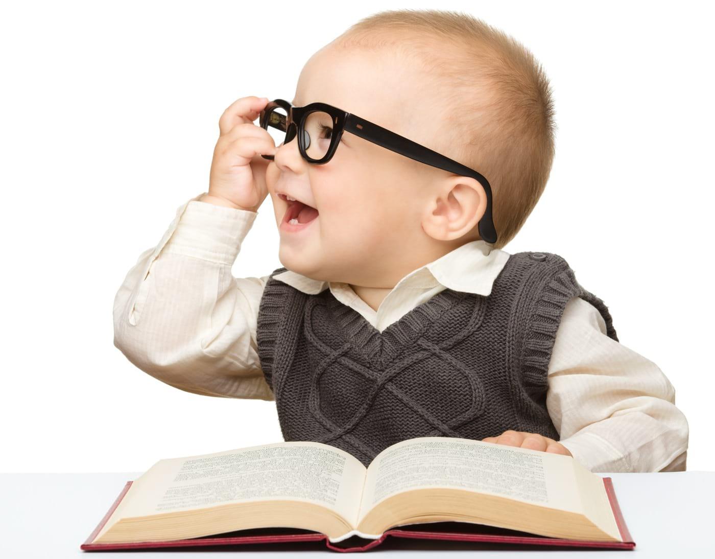 Małe dziecko wokularach czyta książkę