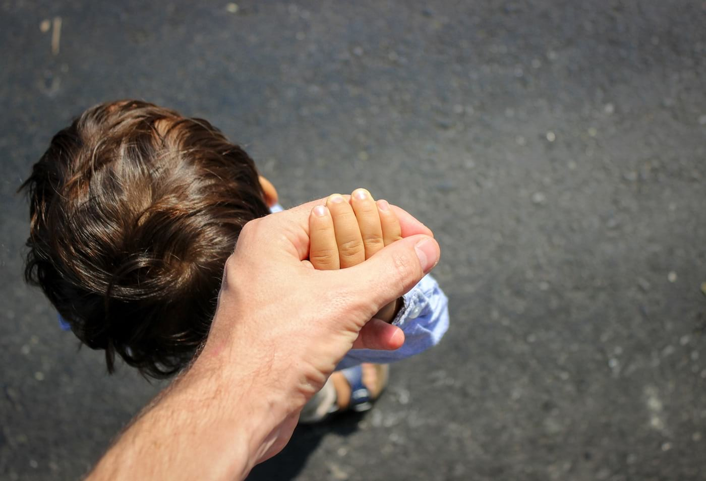 Dziecko prowadzi dorosłego zarękę