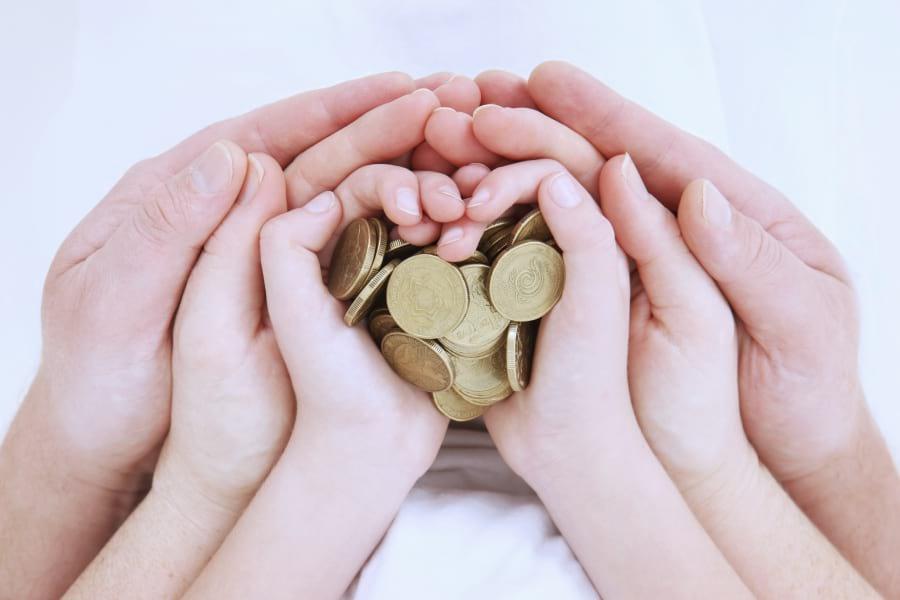 dłonie-dziecka-i-rodziców-pełne-monet