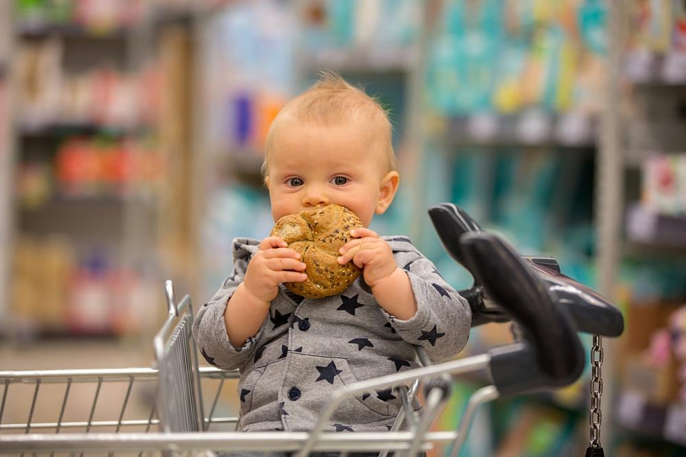 niemowle-w-wozku-sklepowym-je-bulke