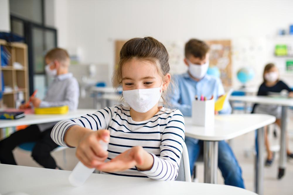 uczennica-w-maseczce-dezynfekuje-rece