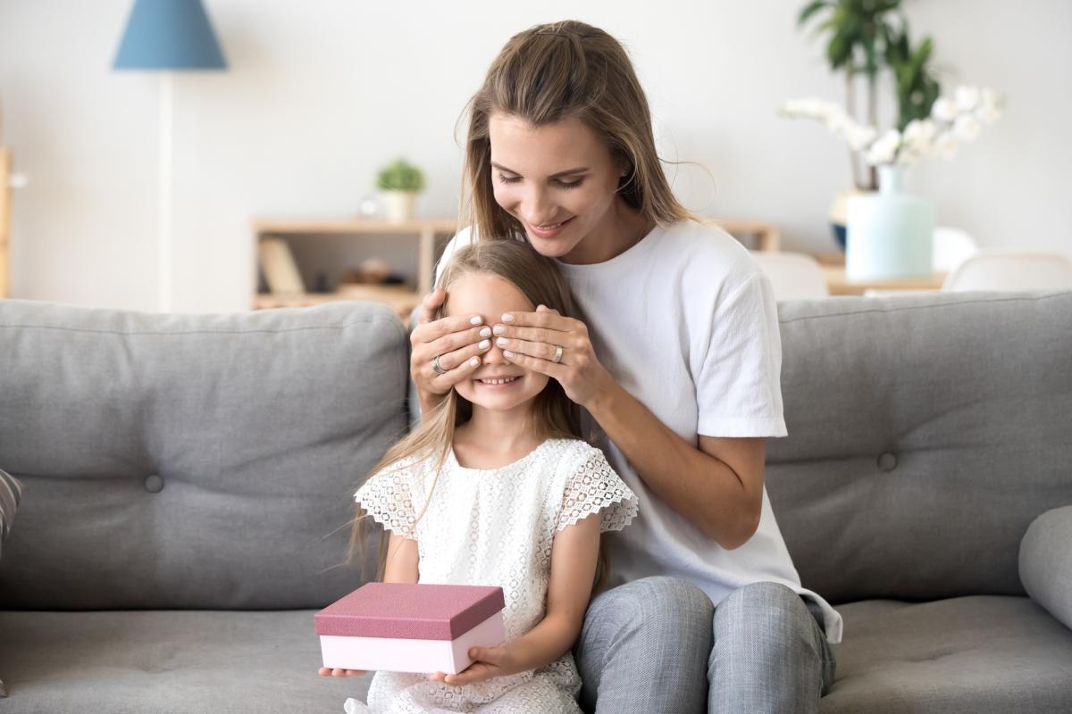 kochajaca mama zasłania oczy córce. dziecko dostaje prezent niespodziankę wpudelku