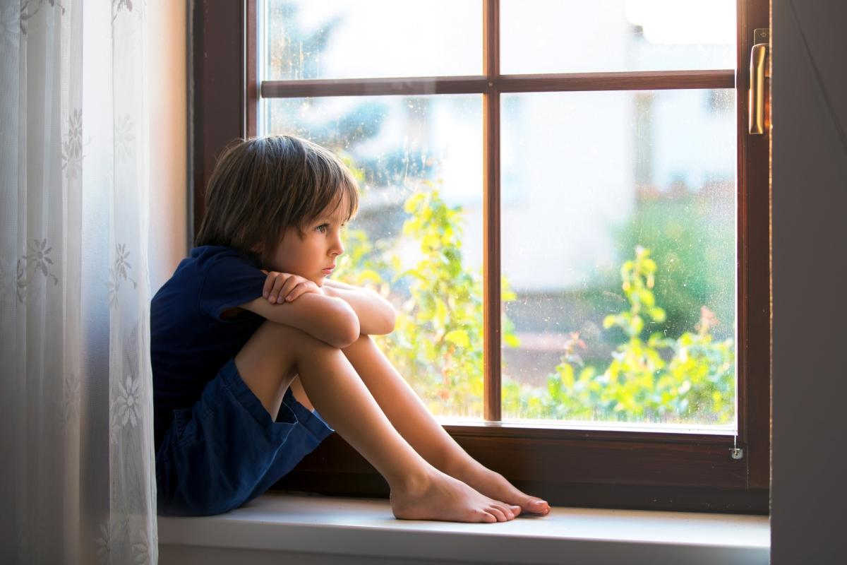 smutny chłopiec siedzi naparapecie ipatrzy przezokno