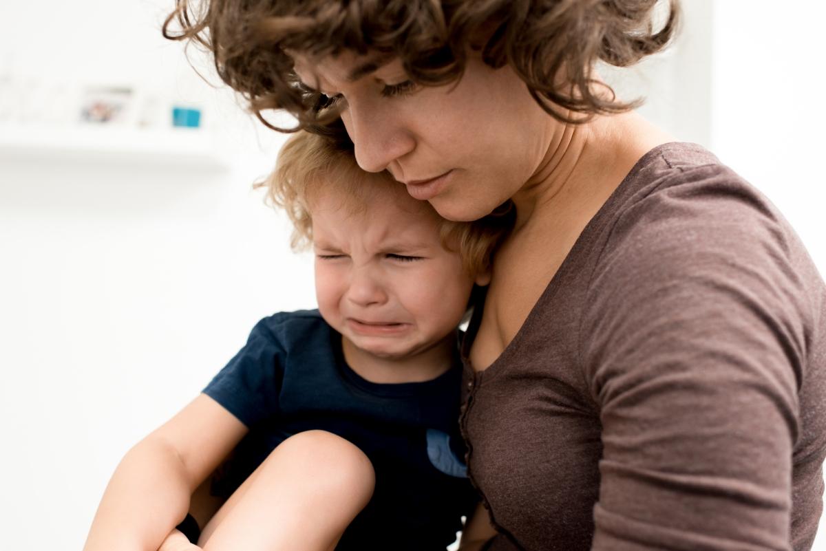 mały chłopiec płacze siedząc nakolanach umamy