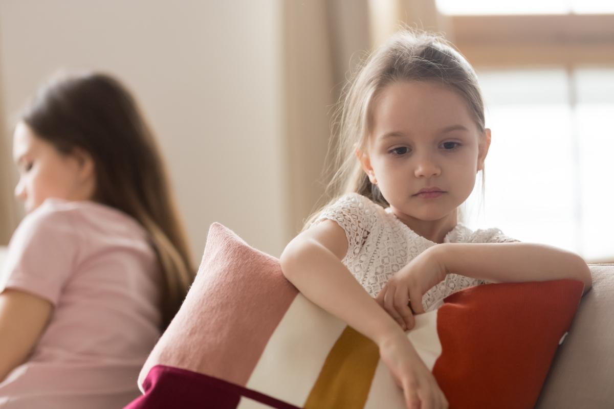 smutna dziewczynka siedzi nakanapie plecami domamy, tuli poduszkę