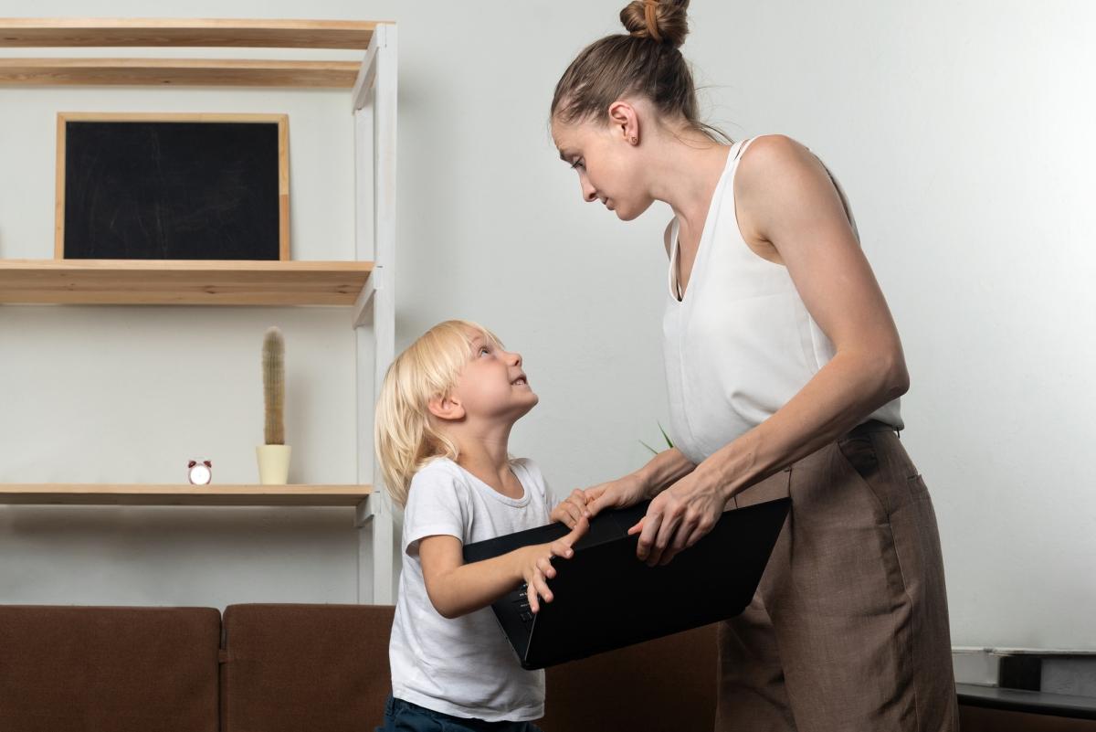 dziecko prosi mamę olaptopa. mama próbuje odebrać synowi komputer