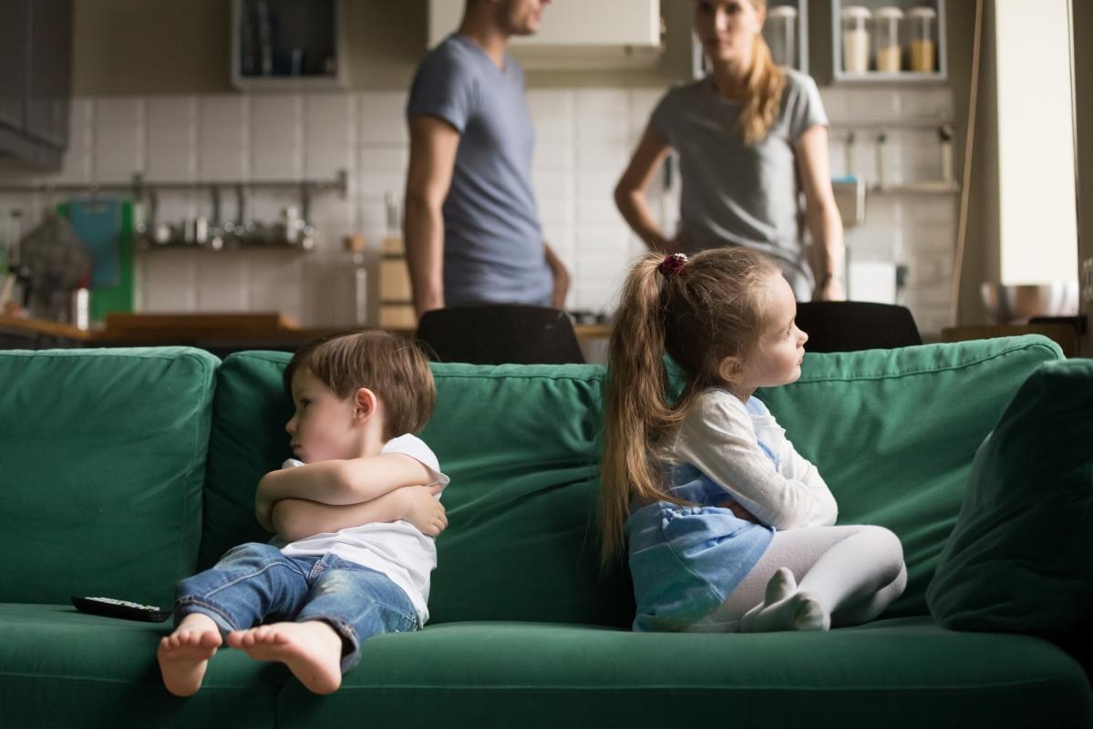 skłócone rodzeństwo siedzi nakanapie plecami dosiebie, rodzice niewiedzą co robić