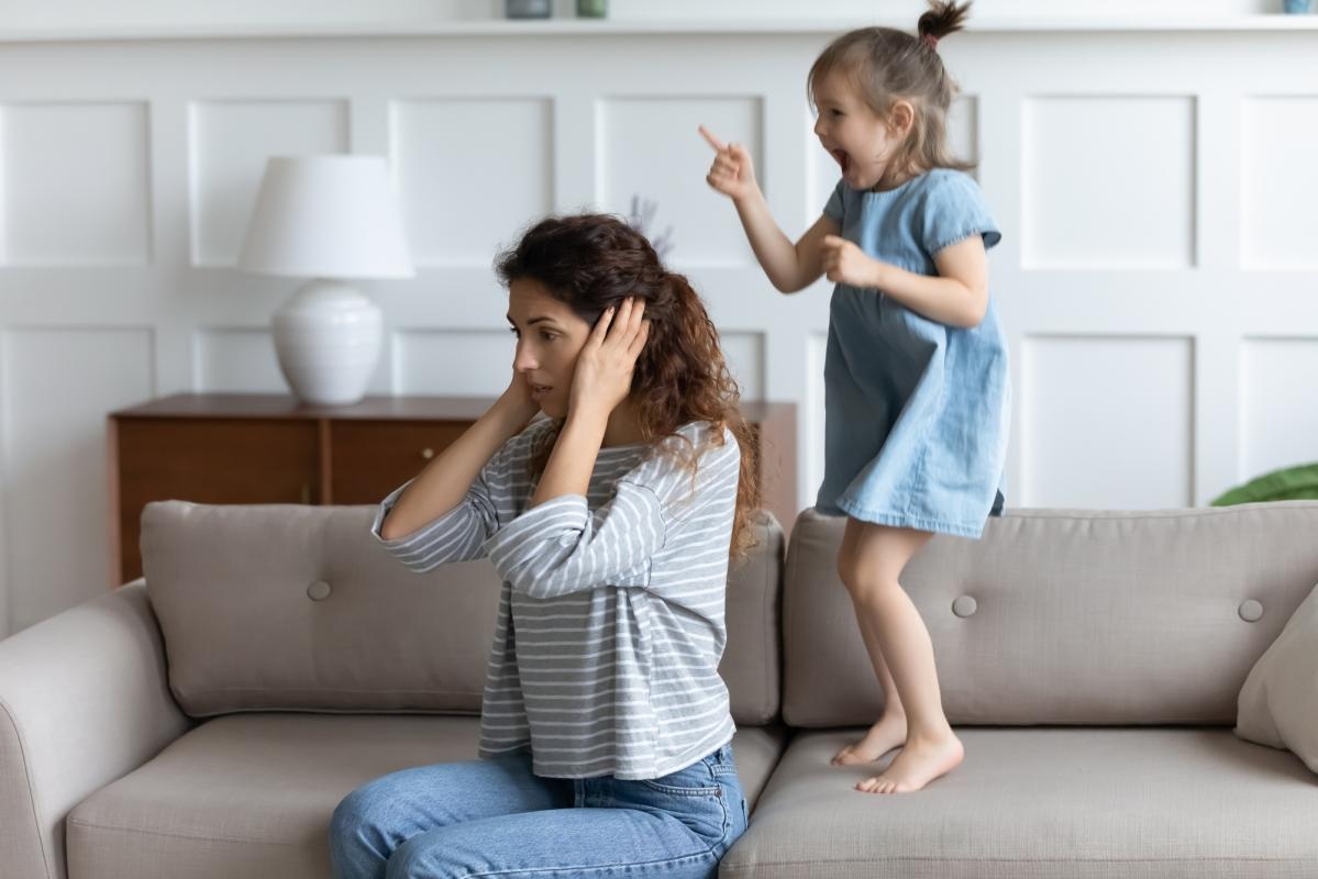 Mama zatyka uszy, podczas gdyjej córka skacze ihałasuje.