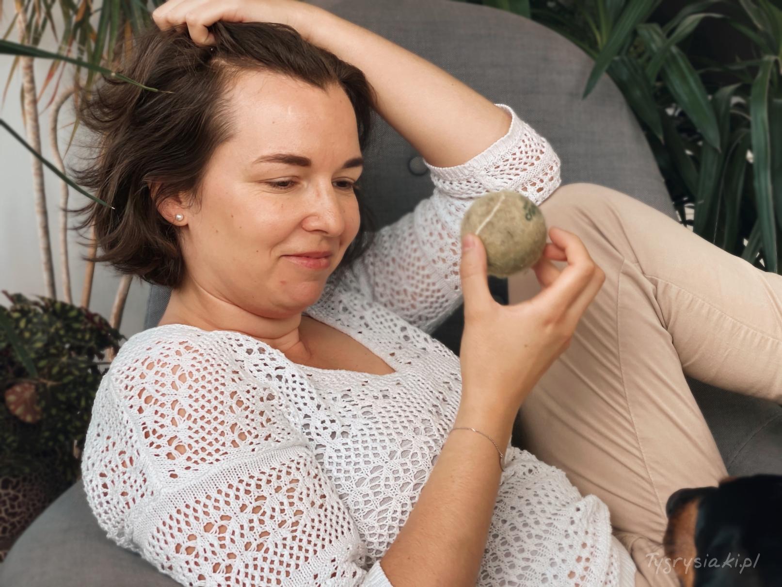 zrelaksowana kobieta siedzi nafotelu, patrzy napsią zabawkę