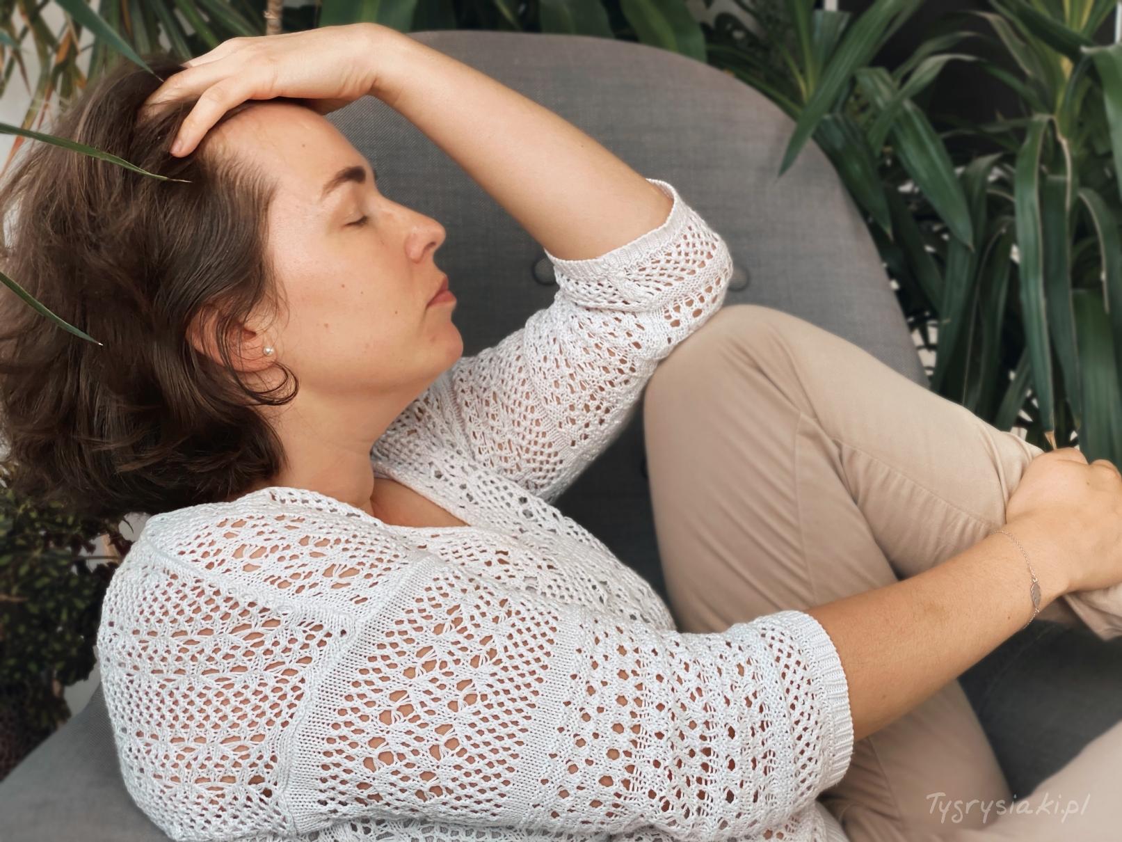 spokojna kobieta odpoczywa nafotelu odgarnia reka wlosy